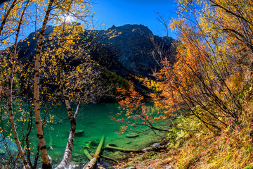 Beautiful autumn landscape with clear green water of a mountain lake and trees with autumn foliage reflected in it