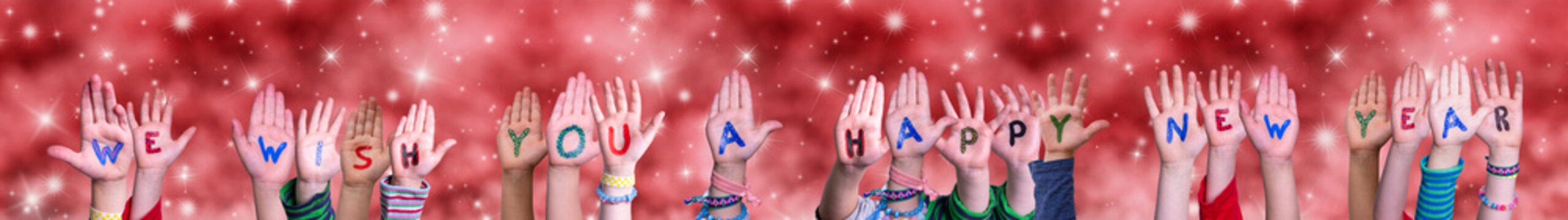 Children Hands Building Colorful English Word We Wish You A Happy New Year. Red Snowy Christmas Winter Background With Snowflakes And Sparkling Lights