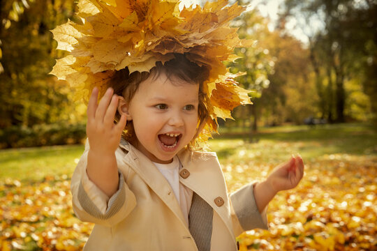 Happy cute baby girl with garland from yellow leaves on her head
