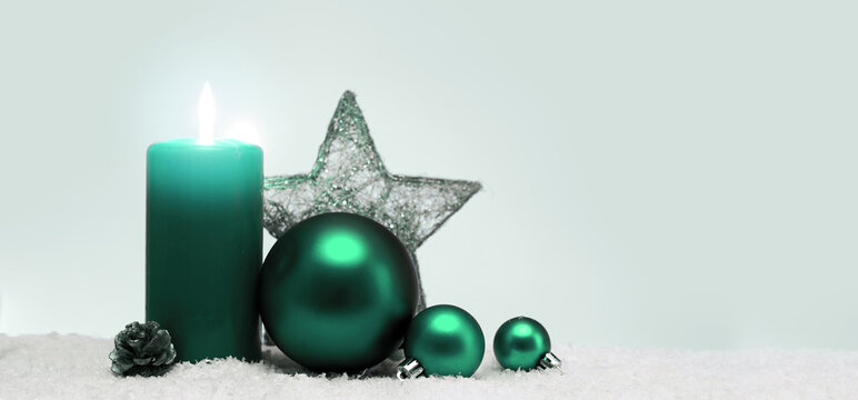 Christmas decoration and green advent candle isolated on blur gray background.