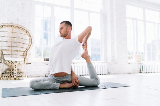 Concentrated male in casual wear doing exercises for stretching muscles feeling recreation and wellness, 20s man enjoying yoga practice in morning at home interior sitting in asana and chilling