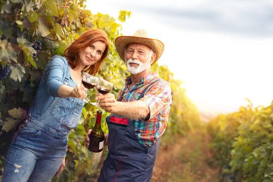 Family on autumn vineyard tasting wine.