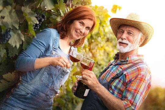 Portrait of couple winemaker toast in vineyard