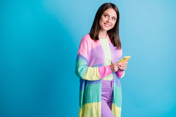 Photo of beautiful brown haired girl hold phone look empty space think creative comment wear purple pants isolated on blue color background Wall mural