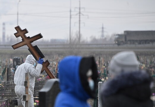 A grave digger carries a cross during the funeral of a person, who presumably died of the coronavirus disease (COVID-19), in Omsk