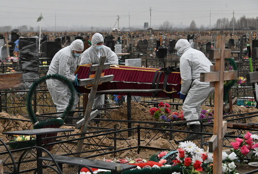 Grave diggers bury a person, who presumably died of the coronavirus disease (COVID-19), in Omsk