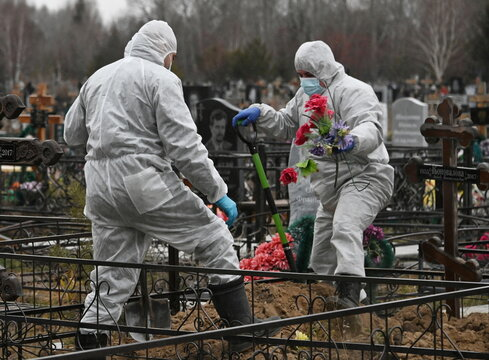 Grave diggers work during the funeral of a person, who presumably died of the coronavirus disease (COVID-19), in Omsk