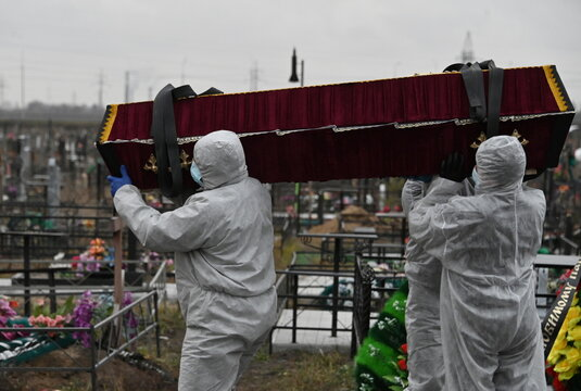 Grave diggers carry the coffin of a person, who presumably died of the coronavirus disease (COVID-19), during a funeral in Omsk
