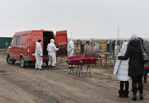 Grave diggers prepare to bury a person, who presumably died of the coronavirus disease (COVID-19), in Omsk