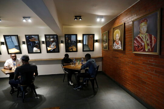 Customers eat their lunch next to paintings including a painted portrait of U.S President Donald Trump wearing a gold-trimmed red agbada, a traditional flowing robe worn by Yoruba men in southern Nigeria, in a upscale restaurant in Lagos
