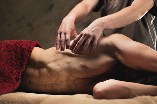 Physiotherapist giving Sports breast massage to bearded athlete in dark room of spa salon