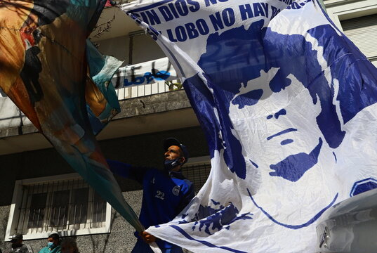 Fans of Argentine soccer great Diego Maradona hang up a banner with his portrait outside a hospital where he was admitted due to being anemic and dehydrated, according to his personal physician, in Buenos Aires
