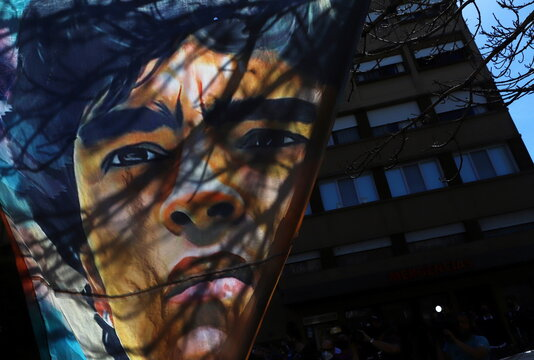 A banner with a portrait of Argentine soccer great Diego Maradona hangs outside the hospital where he was admitted due to being anemic and dehydrated, according to his personal physician, in Buenos Aires