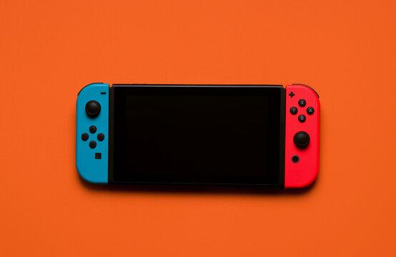 Nintendo Switch on an orange background. editorial