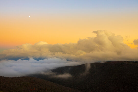The moon and fog banks sit over the Blue Ridge Mountains of North Carolina.