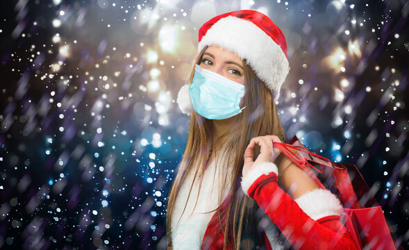 Female Santa Claus shopping under the snow wearing a mask due to coronavirus pandemic