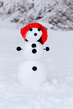 Snowman Dressed with red scarf and hat in the snow outside under the snow