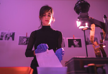 Female photographer developing film and printing photographs in traditional process in darkroom....