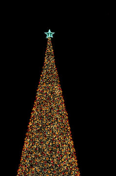 christmas tree with decorates balls and large beautiful star at the top in night