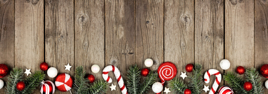 Christmas border of red and white decorations with tree branches. Top view on a dark wood banner background with copy space.