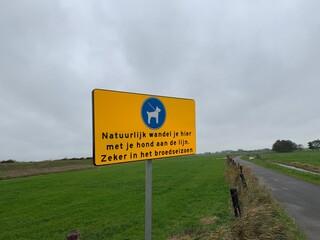 Wall Murals Dog Road sign in Dutch language. Walk your dog with the leash here, especially in the breeding season. (natuurlijk wandel je hier met je hond de lijn. zeker in het broedseizoen). Marken / Netherlands.
