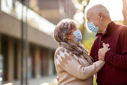 Portrait of senior couple wearing protective face masks outdoors