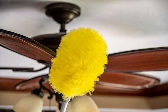 Using a wand feather duster to remove and clean dust from a ceiling fan