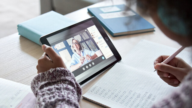 African american school kid child girl holding digital tablet talking to remote teacher tutor on social distance video conference call study online virtual class learning at home, over shoulder view.