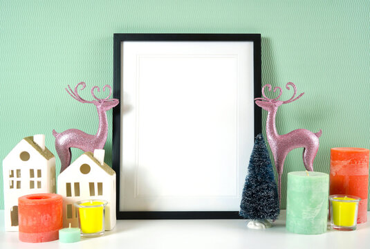 Christmas decorated poster empty frame with modern pastel colors decorations, reindeers and candles against a home interior seafoam green wall with copy space for your text or design here.