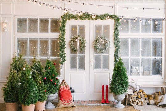 Winter rustic interior decorated for New year with Christmas trees. Winter exterior of a country house with Christmas decorations in rustic or classic style. Christmas eve