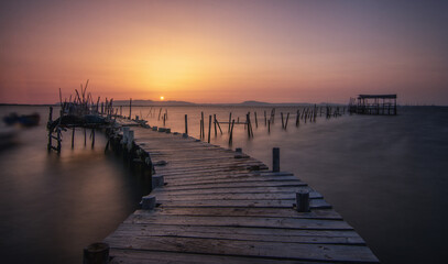 Beautiful scenery of a wooden dock in a port in Carrasqueira, Comporta, Portugal at sunset