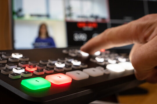 Professional equipment for live video streaming, man pushes button, monitor with split screen