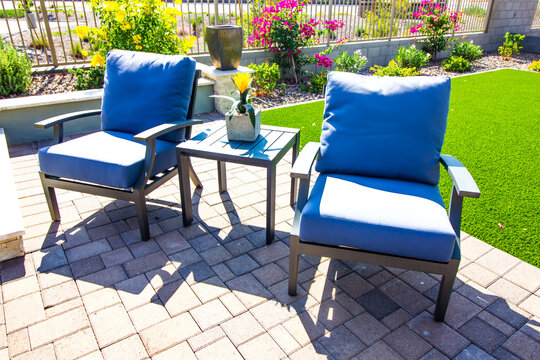 Two Arm Chairs With Blue Cushions & Small Table On Rear Patio Pavers