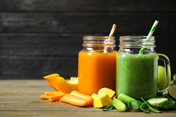 Delicious vegetable juices and fresh ingredients on wooden table. Space for text
