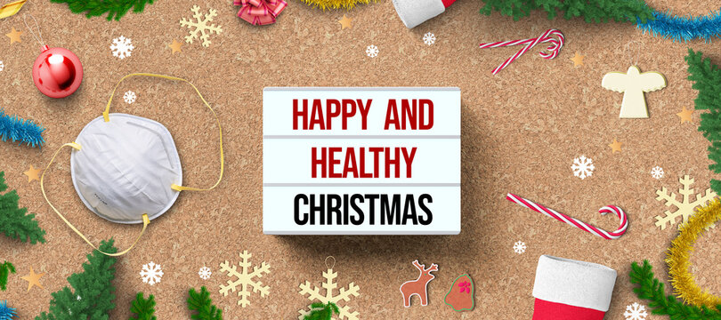 christmas decoration on cork background and lightbox with message HAPPY AND HEALTHY CHRISTMAS