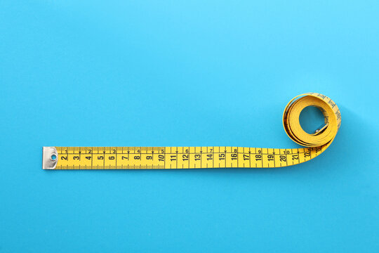 Yellow measuring tape on light blue background, top view