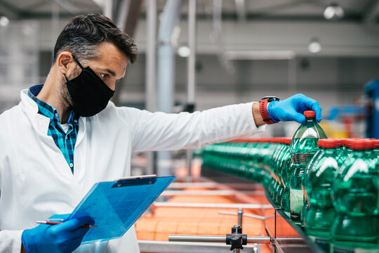 Male worker in bottling factory checking water ottles before shipment. Inspection quality control.