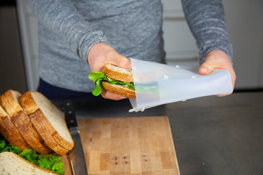 A women prepares lunch and puts a sandwich into a food-grade silicone bag as part of a zero-waste lifestyle to replace plastic bags