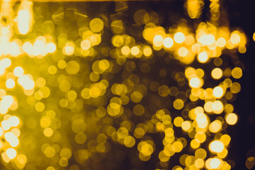 Gold bokeh from light in water with black background