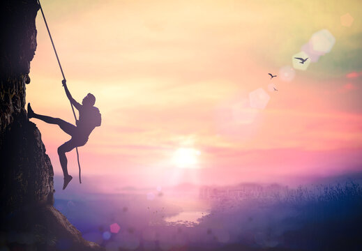Adventure concept: Silhouette bold heroic man try to climb with rope over natural rocky wall wide valley autumn sunset mountain background