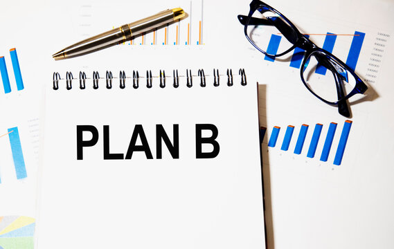 The text in the PLAN B notebook, around there are graphics, glasses and a pen.
