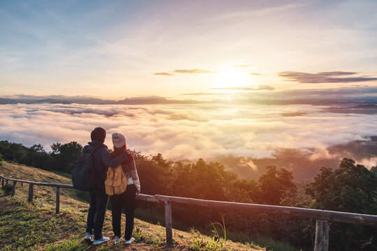Young couple travelers looking at the sunrise and the sea of mist on the mountain in the morning, Travel lifestyle concept