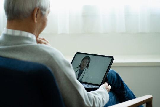 テレビ電話で外国人女性医師と話すシニア男性
