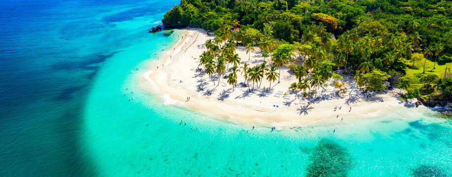 Vacation background. Travel concept. Aerial drone view of beautiful caribbean tropical island with palms and turquoise water. Banner wide format