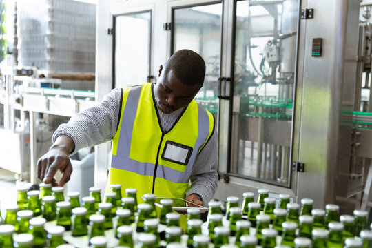African American worker man in a brewery and bottles of beer