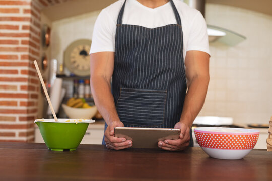 Caucasian man standing in a kitchen and wearing apron