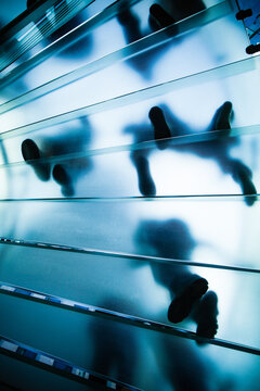 Footsteps blurred through frosted blue glass staircase.