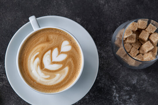 aromatic cappuccino in a white cup on a dark background.