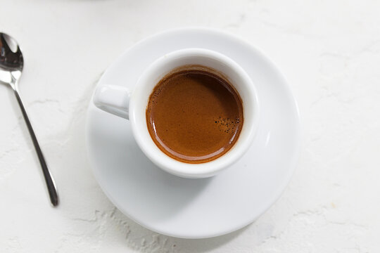 fresh strong espresso in a white cup on a white background, morning with coffee in a coffee shop