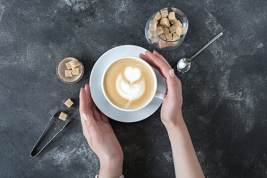 beautiful female hands hold a white cup with cappuccino.
